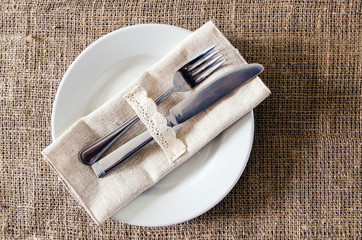 Empty dish, knife and fork on a napkin of burlap
