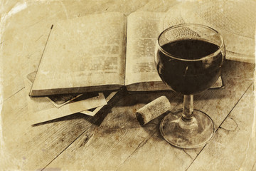 red wine glass and old book on wooden table.  black and white
