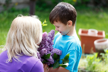 Little boy give lilac to mom mother's day