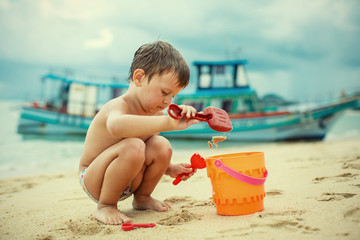A boy playing on the beach with sand