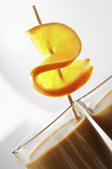 Glas Latte Macchiato mit  Orangenscheibe am Spiess