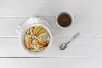 Tasse Kaffee, Schale mit Haferbrei, Äpfel, Bananen, Sesamkörner