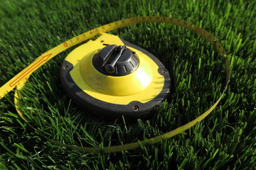 Measuring tape lying on the fresh mown lawn grass