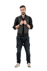 Young confident hipster holding his vest looking at camera