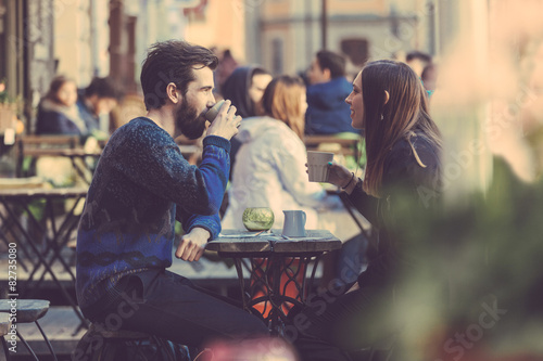 Hipster couple drinking coffee in Stockholm old town. Poster