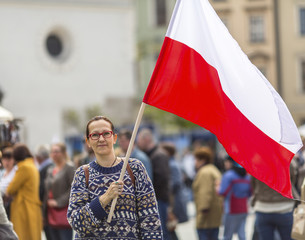 Woman on the street holding a flag of the Republic of Polish..