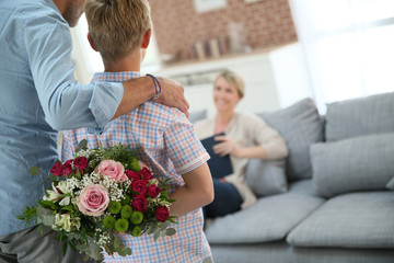 Son hiding bouquet to surprise mommy on mother's day
