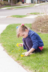 little girl playing with dandelions outside