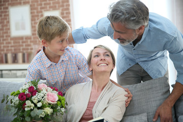 Young boy giving flowers to mommy for mother's day