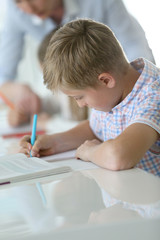 Schoolboy in classroom writing on notebook