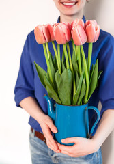 girl holds jug with tulips