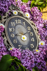Clock surrounded by spring flowers. Lilac flowers