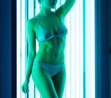 Young woman sunbathing in solarium