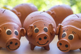 Clay piggy banks in a close-up photo.