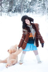 Beautiful girl on winter snowy forest background with teddy bear