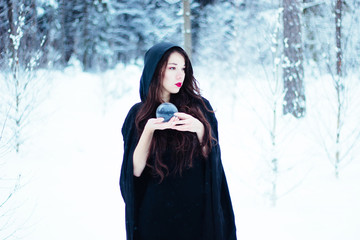 Beautiful witch in black cloak with magiс ball