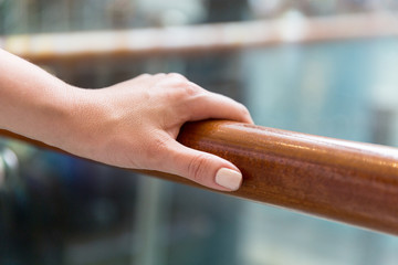 close up of woman hand holding to railing