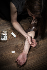 Young woman injecting drugs, social problem concept photo.