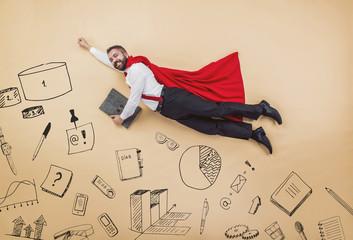Manager in cloak of superman. Studio shot on a beige background.