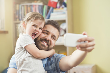 Young father with his cute little daughter taking selfie