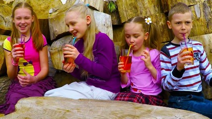 four children 7-10 years old laugh, talk and drink apple juice