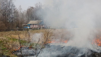 Wildfire in field near house