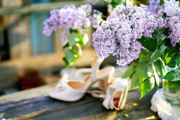 Bouquet of lilac on soft background with bride's shoes