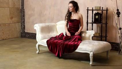 Woman in vintage room posing on sofa