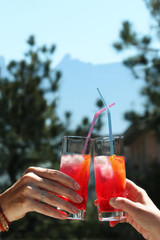two women's hands holding cocktails saying cheers