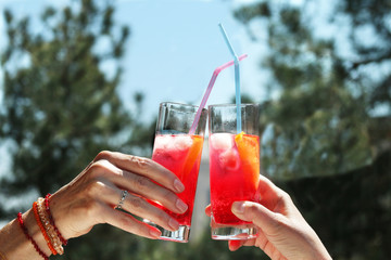 two ladies hands holding cocktails say cheers