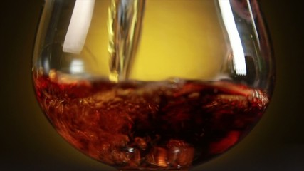 Cognac pouring from bottle into glass with splash on yellow