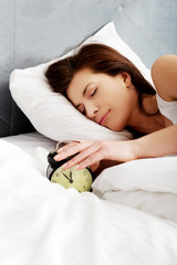 Woman switches off alarm clock.