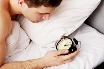 Man with alarm clock in bedroom.