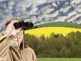 Homme avec jumelles sur terres agricoles