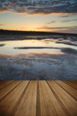 Vibrant sunrise landscape reflected in low tide water on beach w