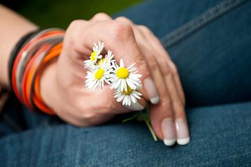jeune femme tenant un bouquet de pâquerettes dans la main