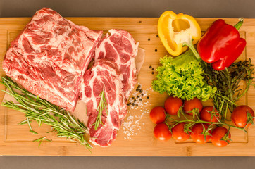 Raw meat with vegetables and spices on wooden background