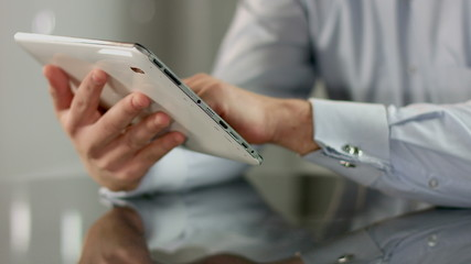 Man scrolling images, reading news on tablet PC, hands closeup