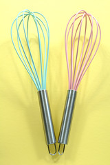 Turquoise and pink kitchen whisks on yellow background