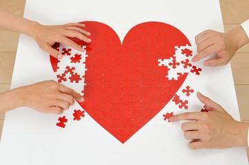 ジグソーパズルの赤いハートを作っている人間の手