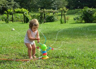 Child playing with a toy sprinkler
