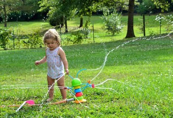 Girl toddler playing with spraying water from sprinkler
