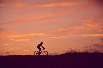 Mann mit Mountainbike fahren Sonnenaufgang