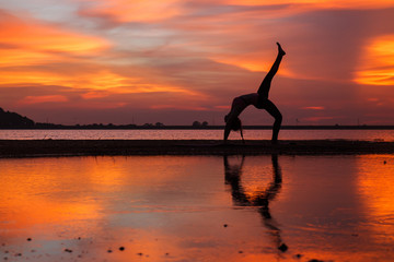 Silhouette of young woman practicing yoga on the lake at sunset