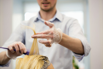 A hairdresser dyeing hair and making a haircut for a blonde girl