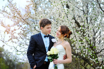 Bride and groom stand near a flowering tree in spring garden