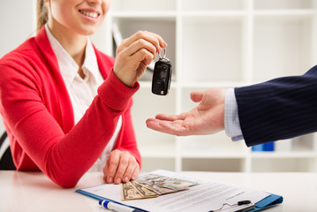 Rental contract. Woman automotive dealer offering key to buyer
