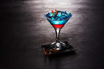 blue cocktail in a glass with ice