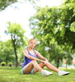 Female athlete resting seated on grass in a park