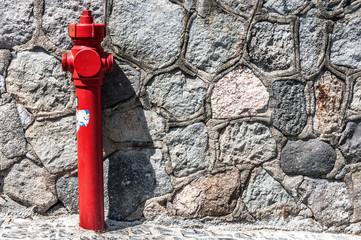 idrante rosso con muro grigio